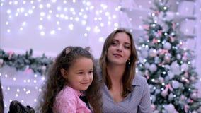 Het jonge aantrekkelijke moeder en dochterzitting koesteren die de camera bekijken die tegen de achtergrond van Kerstmis glimlach stock videobeelden