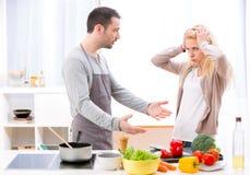 Het jonge aantrekkelijke paar die hebben debatteert terwijl het koken Royalty-vrije Stock Afbeeldingen