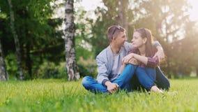 Het jonge aantrekkelijke paar ontspannen in het park, het koesteren, het glimlachen stock footage