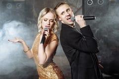 Het jonge aantrekkelijke paar zingen tegen de rook in een donkere ruimte royalty-vrije stock fotografie