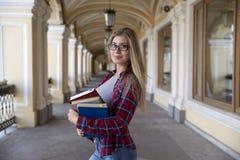 Het jonge aantrekkelijke studentenmeisje met boeken glimlachen die bekijken kwam royalty-vrije stock afbeeldingen