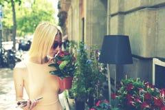Het jonge aantrekkelijke vrouw ruiken bloeit terwijl het winkelen de installaties in stedelijke stoepplantkunde winkelen Stock Afbeeldingen
