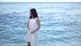 Het jonge aantrekkelijke vrouw stellen op het strand stock video