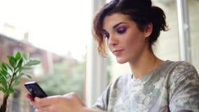 Het jonge aantrekkelijke vrouw texting op haar mobiele telefoon in koffie en het glimlachen Vrouw die app op smartphone in koffie stock footage