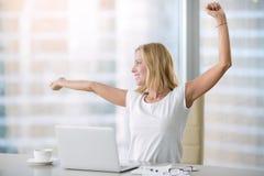 Het jonge aantrekkelijke vrouw uitrekken zich bij bureau Royalty-vrije Stock Afbeelding