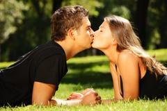 Het jonge aardige paar kussen in het park Stock Afbeelding