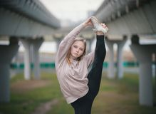 Het jonge acrobaatmeisje in beige hoodie voert uitrekkende status op één been tegen de achtergrond van de brug uit stock fotografie
