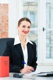 Advocaat die in bureau nota's in een dossier maken Stock Foto's