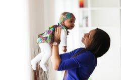 Het jonge Afrikaanse Amerikaanse moeder spelen met haar babymeisje stock foto