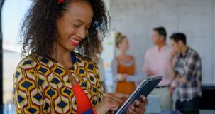 Het jonge Afrikaanse Amerikaanse vrouwelijke uitvoerende werken aan digitale tablet in modern bureau 4k stock footage