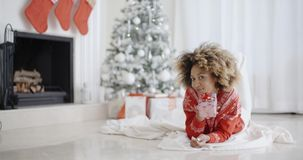 Het jonge Afrikaanse meisje liggen die haar Kerstmisgift bekijken stock videobeelden