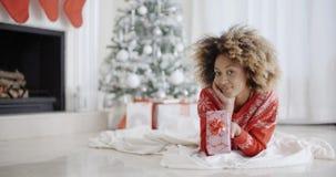 Het jonge Afrikaanse meisje liggen die haar Kerstmisgift bekijken stock footage