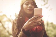 Het jonge Afrikaanse meisje van Amerika in park die slimme telefoon met behulp van De nadruk is o stock foto