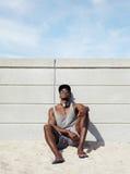 Het jonge Afrikaanse mens ontspannen op het strand Stock Afbeelding