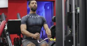 Het jonge Afro-Amerikaanse mannetje voert een oefening op de simulator uit stock videobeelden