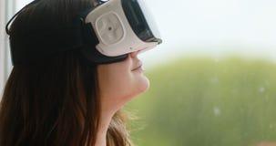 Het jonge apparaat van de werkelijkheids digitale glazen van de vrouwenslijtage virtuele, het glimlachen mooi de technologieverma stock videobeelden