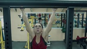 Het jonge atletische meisje, atletisch bouwt op de bar op stock videobeelden