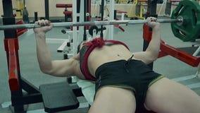 Het jonge atletische meisje leidt de spieren van de borst op, uitvoerend de oefening van de bankpers Langzame Motie stock video