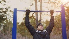 Het jonge atletische mens doen trekt oefening in openlucht uit in de winterpark Royalty-vrije Stock Foto's