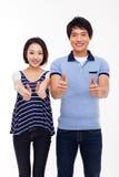 Het jonge Aziatische die paar toont duimen op witte achtergrond worden geïsoleerd. Royalty-vrije Stock Afbeelding