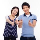 Het jonge Aziatische die paar toont duimen op witte achtergrond worden geïsoleerd. Royalty-vrije Stock Afbeeldingen