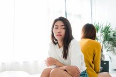 Het jonge Aziatische lesbische paar debatteert en draait hun terug naar elkaar tijdens de periode van droevig in de slaapkamer Royalty-vrije Stock Foto