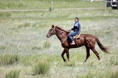 Het jonge Aziatische meisje berijdt haar zuiver rassenpaard in de steppe van Kazachstan royalty-vrije stock afbeelding