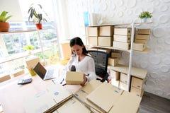 Het jonge Aziatische meisje is freelancer Start kleine het bedrijfseigenaar schrijven adres op kartondoos op werk, die het winkel royalty-vrije stock fotografie