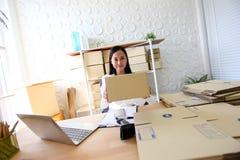 Het jonge Aziatische meisje is freelancer Start kleine het bedrijfseigenaar schrijven adres op kartondoos op werk, die het winkel stock foto's
