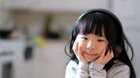 Het jonge Aziatische meisje genieten die aan muziek op haar hoofdtelefoon luisteren stock video