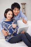 Het jonge Aziatische paar die stootkussenPC met behulp van en toont duimen Stock Afbeeldingen