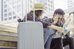 Het jonge Aziatische Paar van reizigers, bekijkt kaart en spanning omdat royalty-vrije stock foto