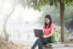 Het jonge Aziatische student openlucht zitten, gebruikend laptop Stock Foto
