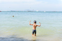 Het jonge Aziatische Thaise jongen spelen op het zandstrand Stock Afbeelding