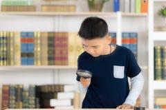 Het jonge Aziatische van de jongens het glimlachen van en greep vergrootglas de bibliotheek is stock foto's