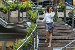 Het jonge Aziatische vrouw spreken op mobiel daalt op de stappen Royalty-vrije Stock Fotografie