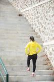Het jonge Aziatische vrouw uitoefenen openlucht in geel jasje, die g aanstoten stock foto's
