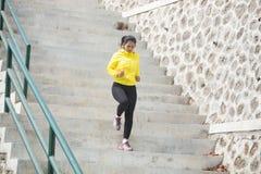 Het jonge Aziatische vrouw uitoefenen openlucht in geel jasje, die g aanstoten stock fotografie
