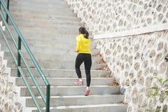 Het jonge Aziatische vrouw uitoefenen openlucht in geel jasje, die g aanstoten royalty-vrije stock foto's