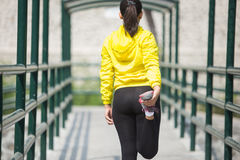 Het jonge Aziatische vrouw uitoefenen openlucht in geel neonjasje, stre royalty-vrije stock fotografie