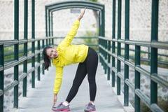 Het jonge Aziatische vrouw uitoefenen openlucht in geel neonjasje, stre royalty-vrije stock afbeelding