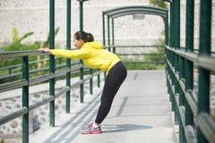 Het jonge Aziatische vrouw uitoefenen openlucht in geel neonjasje, stre stock fotografie