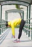 Het jonge Aziatische vrouw uitoefenen openlucht in geel neonjasje, stre stock foto