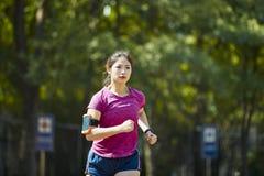 Het jonge Aziatische vrouwelijke atleet lopen stock fotografie