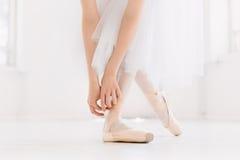 Het jonge ballerina dansen, close-up op benen en schoenen, die zich in pointepositie bevinden stock afbeelding