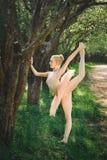 Het jonge ballerina uitrekken zich en oefent in openlucht vóór dans uit stock foto's