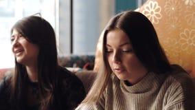 Het jonge bedrijf heeft pret en eet in bar het roken van een waterpijp, die in een oosters restaurant communiceren stock video