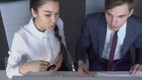 Het jonge bedrijfspaar werkt voorzijde van computer, mens en vrouw die nieuw project 4k de bespreken, zittend bij bureau, het lez stock videobeelden