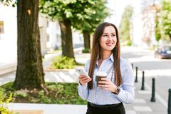 Het jonge Bedrijfsvrouw Gebruiken telefoneren en het Drinken de Koffie terwijl het Lopen stock foto's