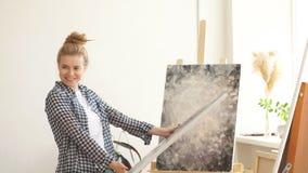 Het jonge begaafde blonde meisje stelt haar artistiek werk voor stock footage